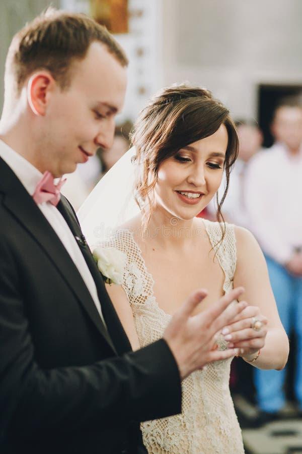 Pares elegantes felices de la boda que intercambian los anillos de bodas durante matrimonio santo en iglesia Novia y novio que po imagenes de archivo