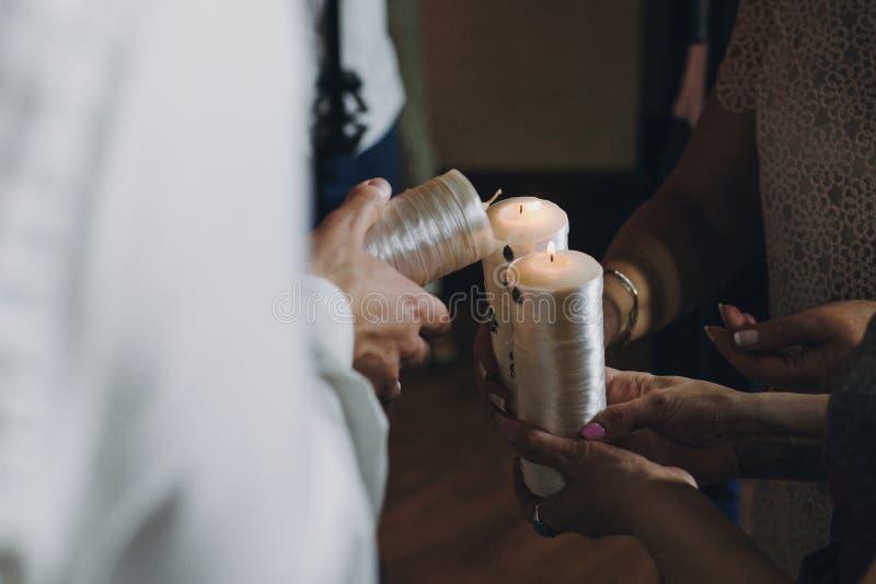 Pares elegantes felices de la boda que llevan a cabo velas con el fuego y encenderlas para arriba con la vela de padres, tradició fotos de archivo