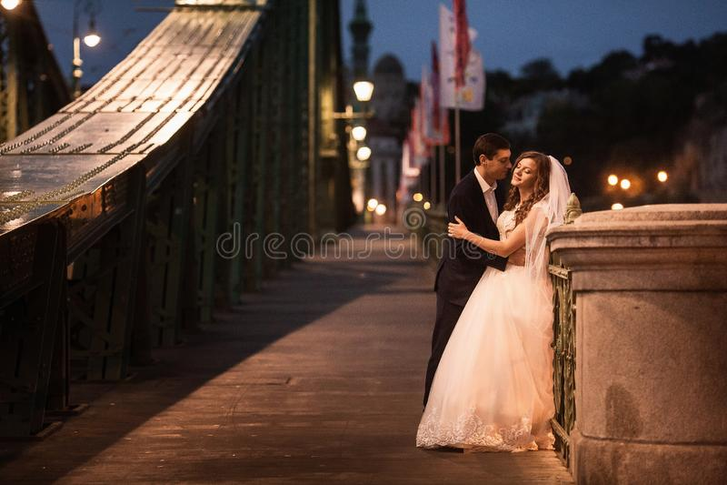 Pares elegantes hermosos jovenes de recienes casados en un puente en Budapest imágenes de archivo libres de regalías