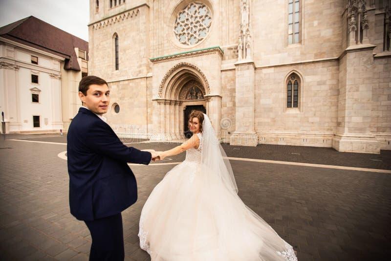 Pares elegantes hermosos jovenes de recienes casados que caminan por el basti?n del pescador en Budapest, Hungr?a foto de archivo