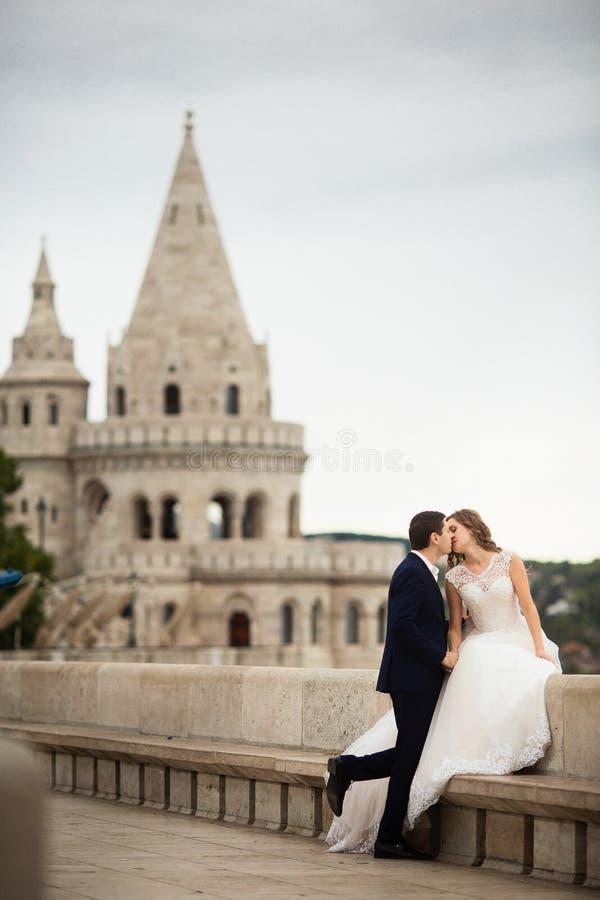Pares elegantes hermosos jovenes de recienes casados que se besan por el basti?n del pescador en Budapest, Hungr?a imagen de archivo