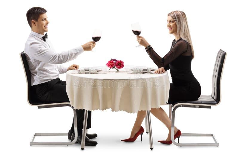Pares elegantes jovenes que tuestan con el vino en una tabla fotos de archivo