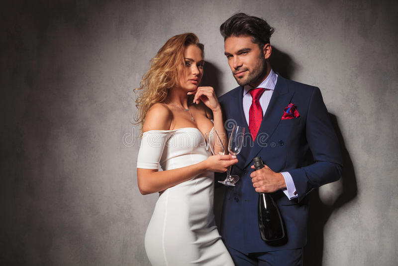 Pares elegantes listos para ir de fiesta con champán fotografía de archivo libre de regalías