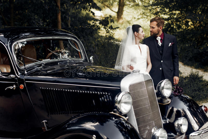 Pares elegantes luxuosos do casamento que guardam as mãos no fundo do chiqueiro foto de stock