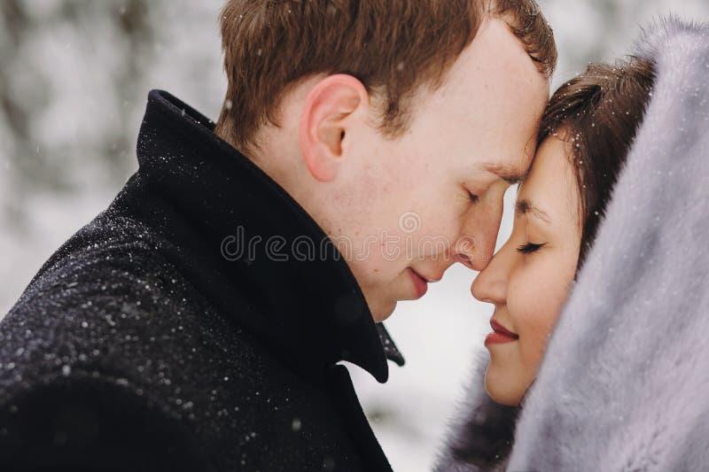 Pares elegantes que abrazan en montañas nevosas del invierno Romant feliz foto de archivo libre de regalías