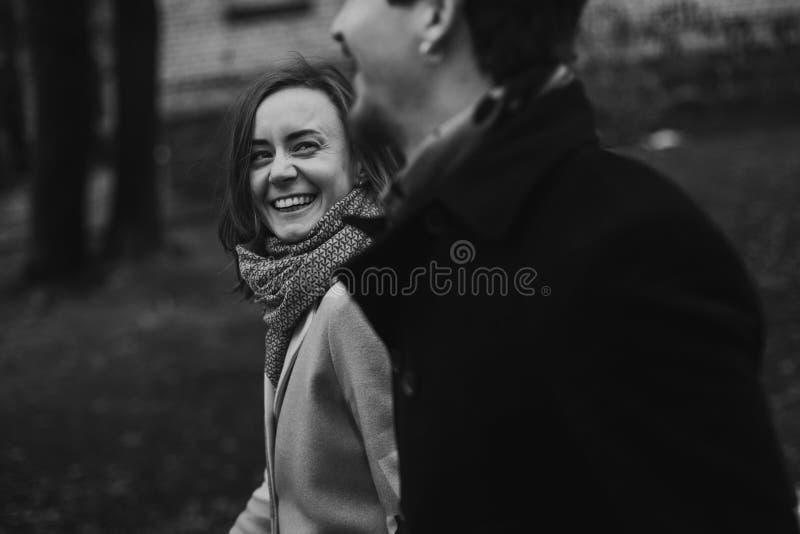 Pares elegantes románticos que caminan y que ríen en parque del otoño Hombre imagenes de archivo