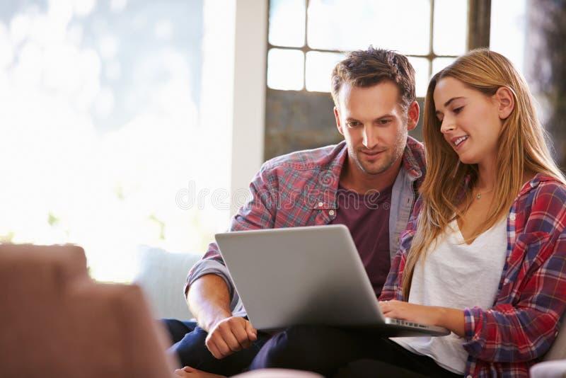 Pares em casa na sala de estar usando o laptop foto de stock