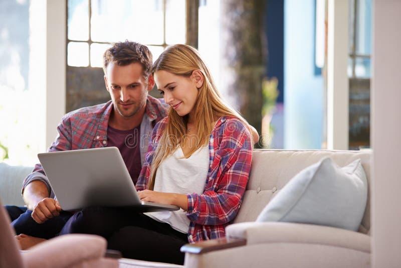 Pares em casa na sala de estar usando o laptop fotografia de stock