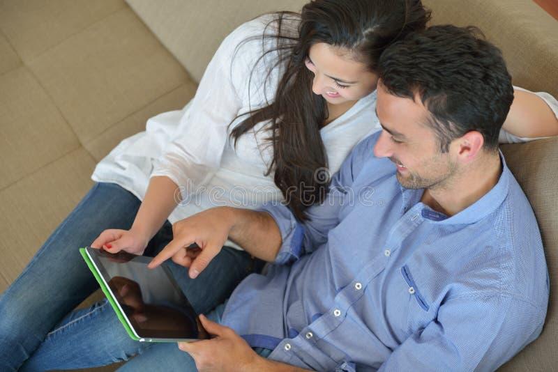 Pares em casa que usam o tablet pc imagem de stock