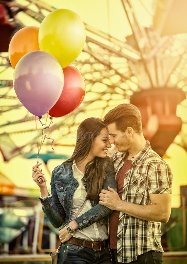 Pares em datar romântico no parque de diversões fotografia de stock royalty free