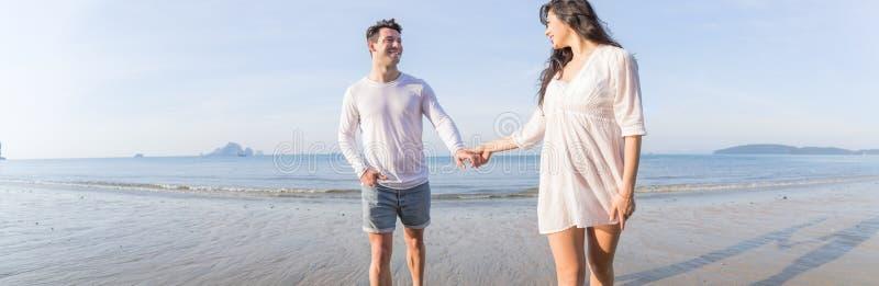 Pares em férias de verão da praia, povos felizes novos bonitos no amor que andam, sorriso da mulher do homem que guarda as mãos imagem de stock