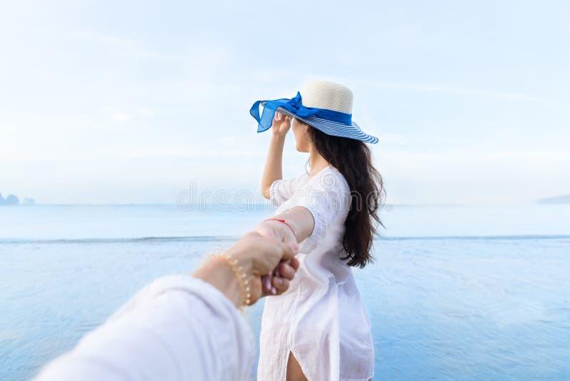 Pares em férias de verão da praia, povos masculinos da mão da posse bonita da moça que olham o mar foto de stock royalty free