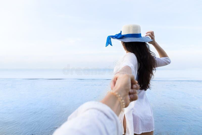 Pares em férias de verão da praia, povos masculinos da mão da posse bonita da moça que olham o mar fotografia de stock
