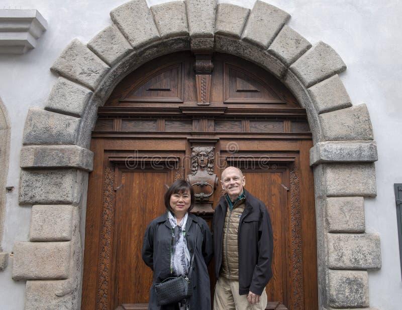Pares em férias na frente de uma porta de madeira ornamentado com aldrava, Cesky Krumlov, República Checa foto de stock
