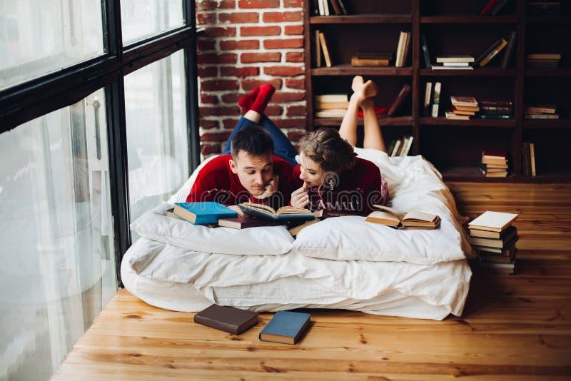 Pares em livros de leitura vermelhos da camiseta do Natal no colchão no hom imagens de stock