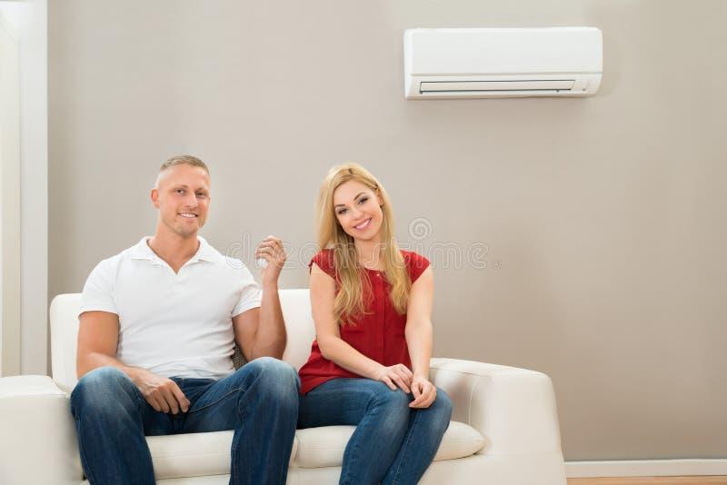 Pares em Sofa Using Air Conditioner fotografia de stock royalty free