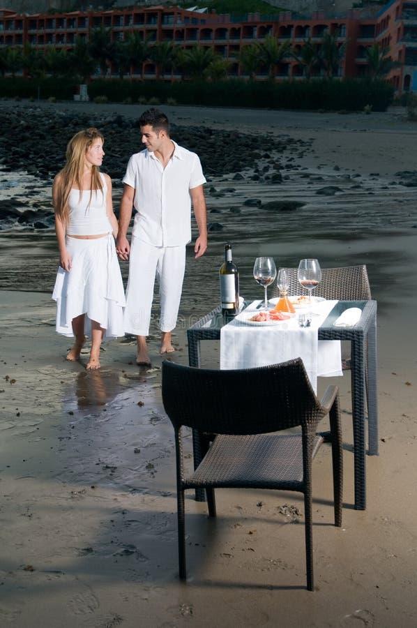 Pares em um jantar romântico na praia imagem de stock