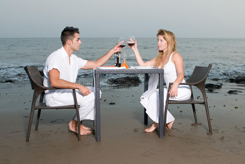 Pares em um jantar romântico na praia imagens de stock
