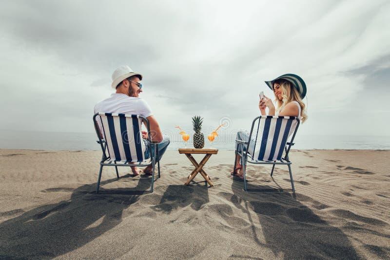 Pares em uma cadeira de plataforma que relaxa na praia foto de stock