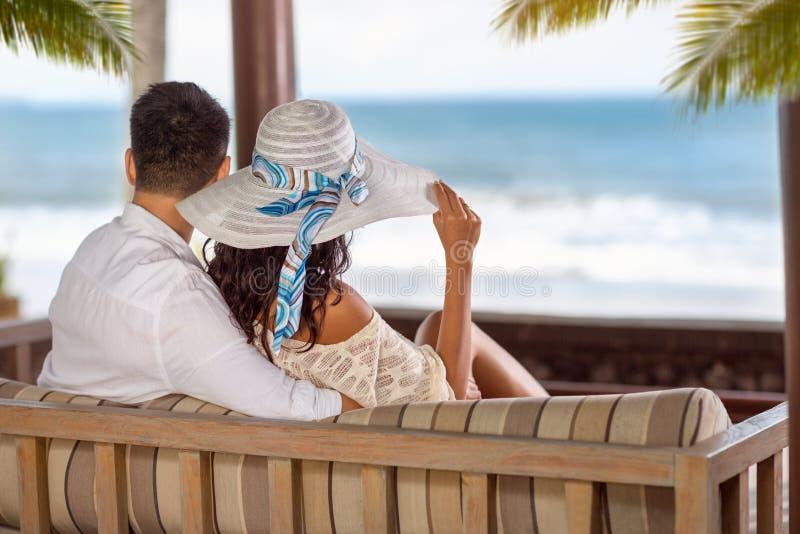 Pares em uma praia tropical na sala de estar do chaise fotos de stock