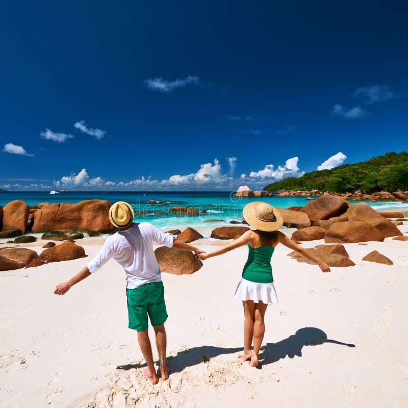 Pares em verde tendo o divertimento em uma praia em Seychelles fotografia de stock royalty free