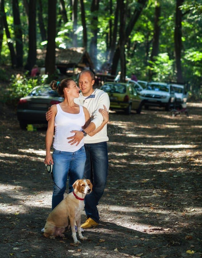 Pares embarazadas con el perrito en un bosque imagen de archivo libre de regalías