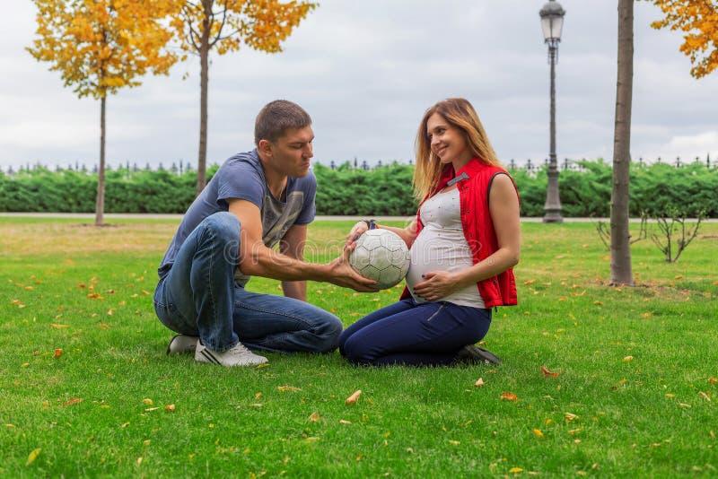 Pares embarazadas con la bola del fútbol imágenes de archivo libres de regalías