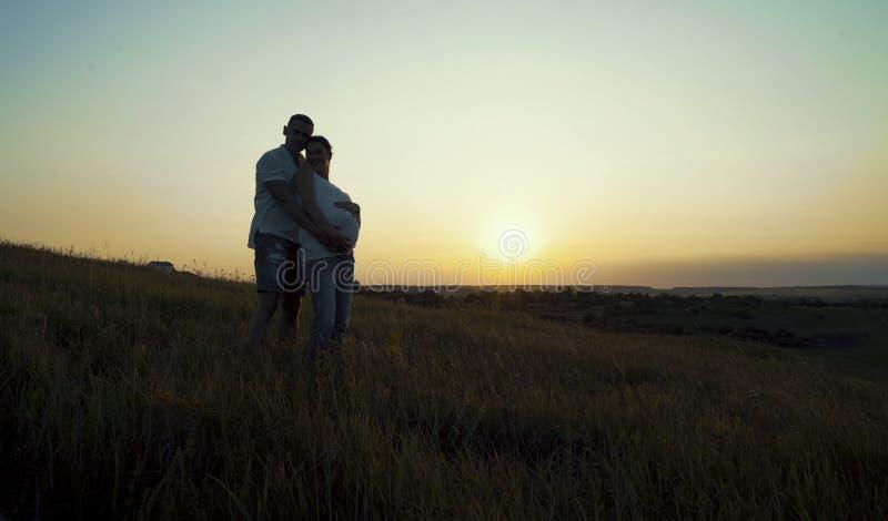 Pares embarazadas felices jovenes románticos que abrazan en naturaleza en la puesta del sol imagen de archivo libre de regalías