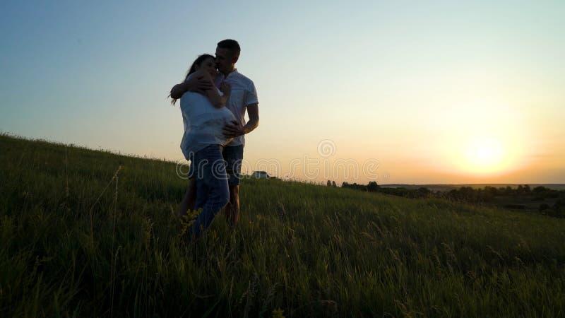 Pares embarazadas felices jovenes románticos que abrazan en naturaleza en la puesta del sol imagenes de archivo