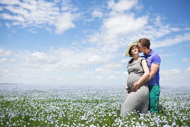 Pares embarazadas hermosos felices jovenes en el campo de lino imágenes de archivo libres de regalías