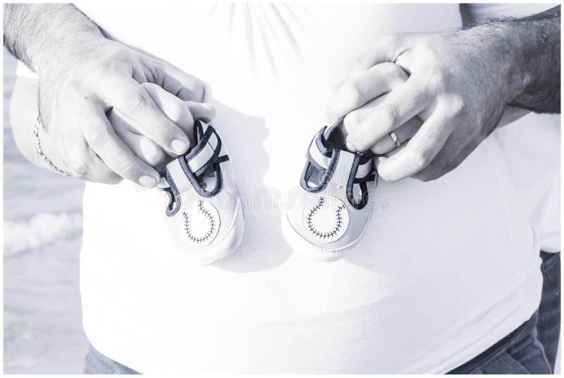 Pares embarazadas que sostienen los zapatos de bebé en la playa imagen de archivo
