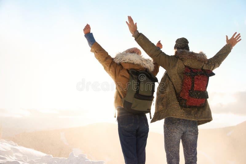 Pares emocionados con las mochilas que disfrutan de Mountain View durante vacaciones del invierno imagenes de archivo
