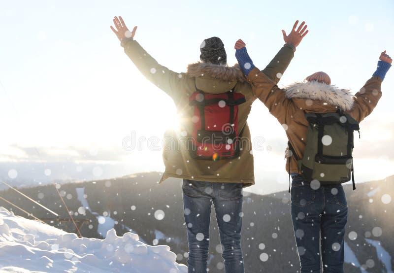 Pares emocionados con las mochilas que gozan de la montaña foto de archivo