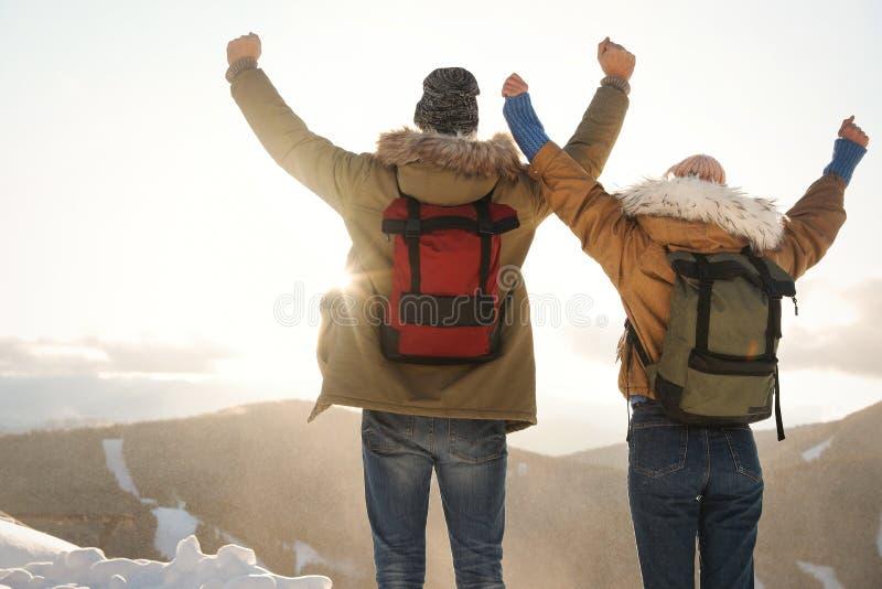 Pares emocionados con las mochilas que gozan de la montaña fotografía de archivo