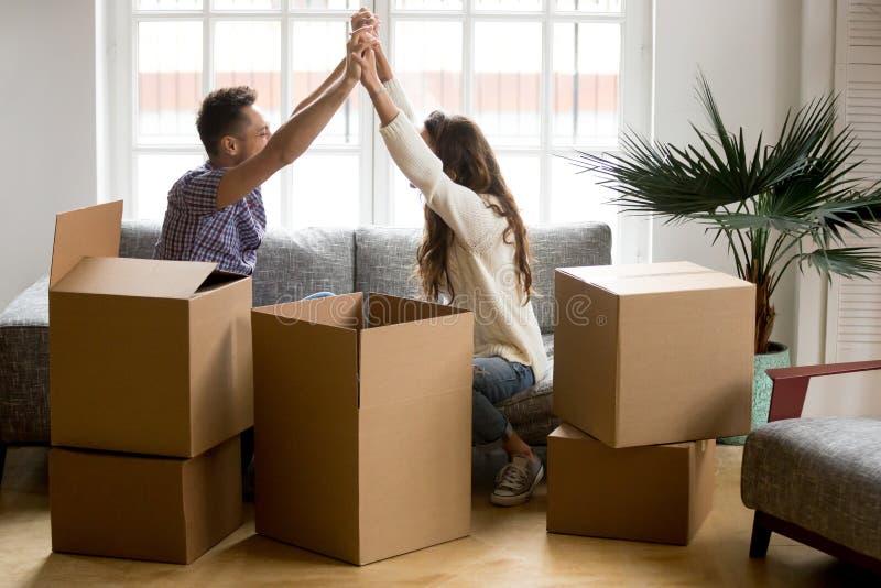 Pares emocionados que llevan a cabo las manos felices de trasladarse a nuevo hogar foto de archivo