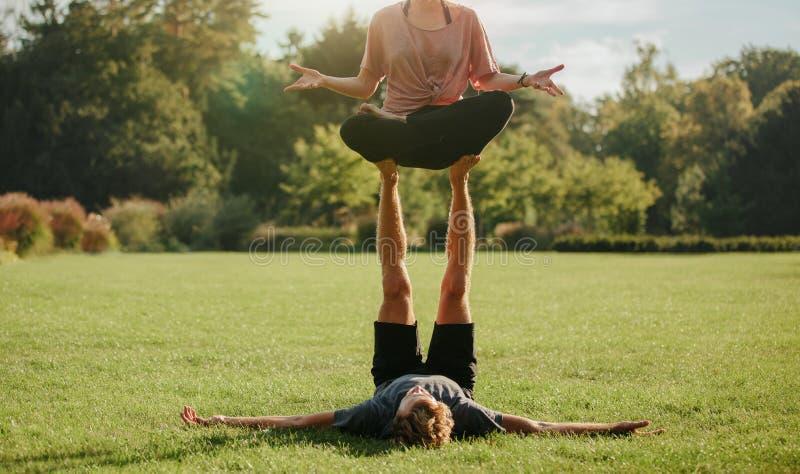 Pares en actitudes practicantes de la yoga de los pares del parque imagen de archivo libre de regalías