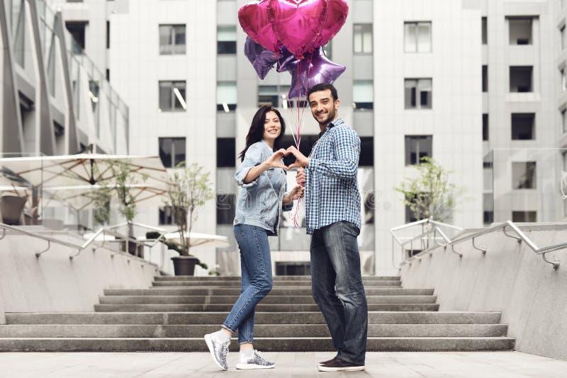 Pares en amor con los globos que ponen las manos juntas imagen de archivo libre de regalías