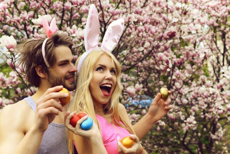 Pares en amor con los oídos del conejito que sostienen los huevos coloridos imagenes de archivo
