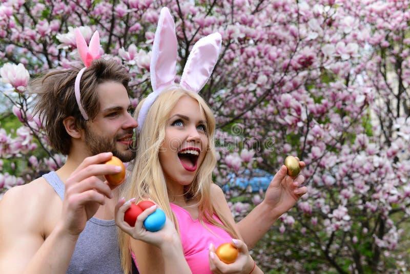 Pares en amor con los o?dos del conejito que sostienen los huevos coloridos imagen de archivo libre de regalías