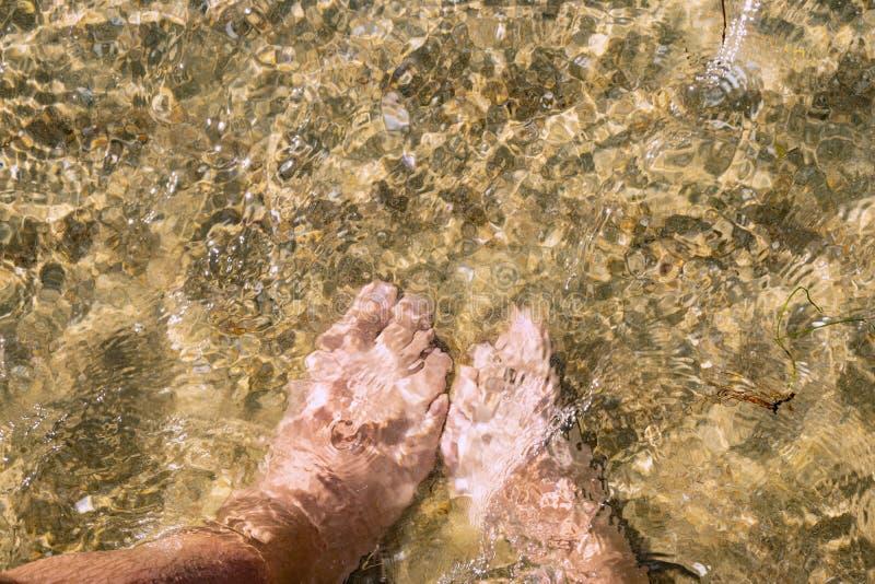 Pares en amor en el lado de mar Ciérrese encima de imagen de las piernas fotos de archivo