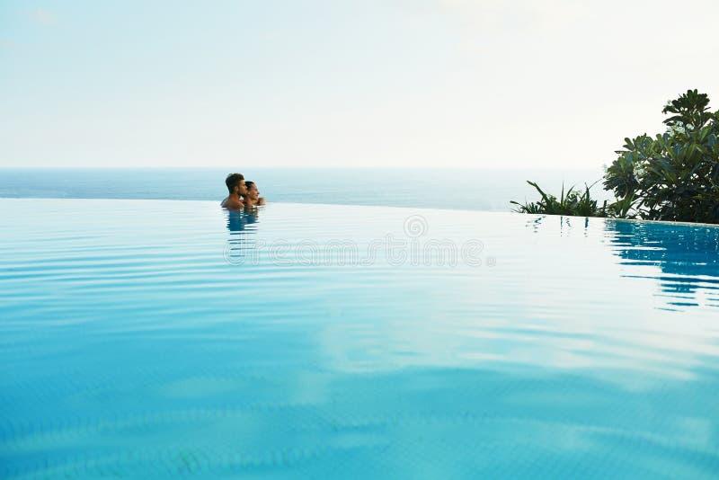 Pares en amor en piscina del centro turístico de lujo en vacaciones de verano románticas fotografía de archivo