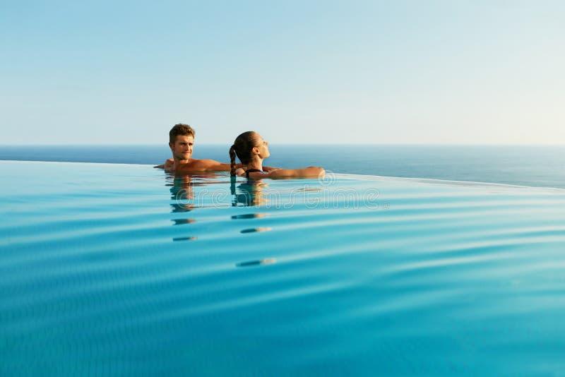 Pares en amor en piscina del centro turístico de lujo en vacaciones de verano románticas fotografía de archivo libre de regalías