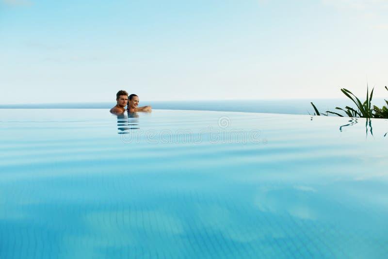 Pares en amor en piscina del centro turístico de lujo en vacaciones de verano románticas imagenes de archivo