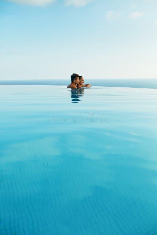 Pares en amor en piscina del centro turístico de lujo en vacaciones de verano románticas imagen de archivo libre de regalías