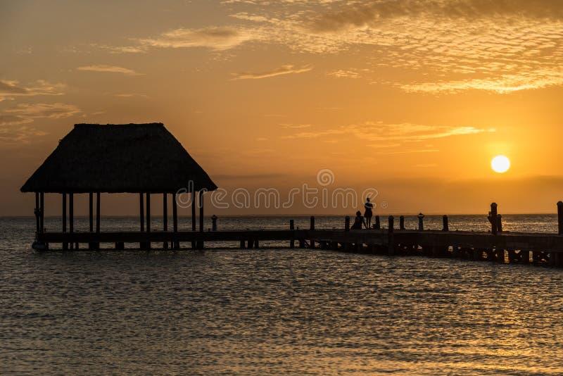 Pares en amor en un palapa de madera del embarcadero que disfruta de puesta del sol en Holbox foto de archivo