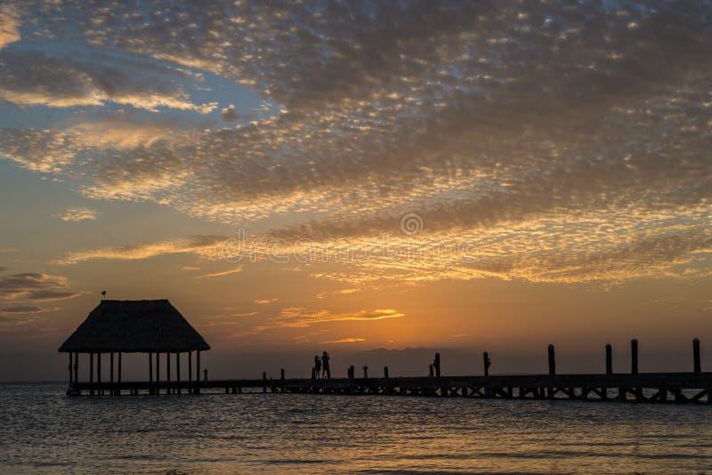 Pares en amor en un palapa de madera del embarcadero que disfruta de puesta del sol en Holbox imagenes de archivo