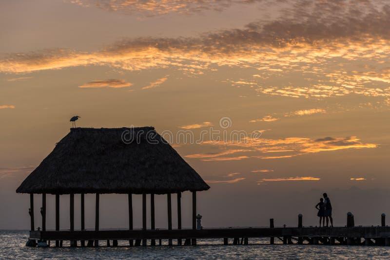 Pares en amor en un palapa de madera del embarcadero que disfruta de puesta del sol en Holbox fotografía de archivo libre de regalías