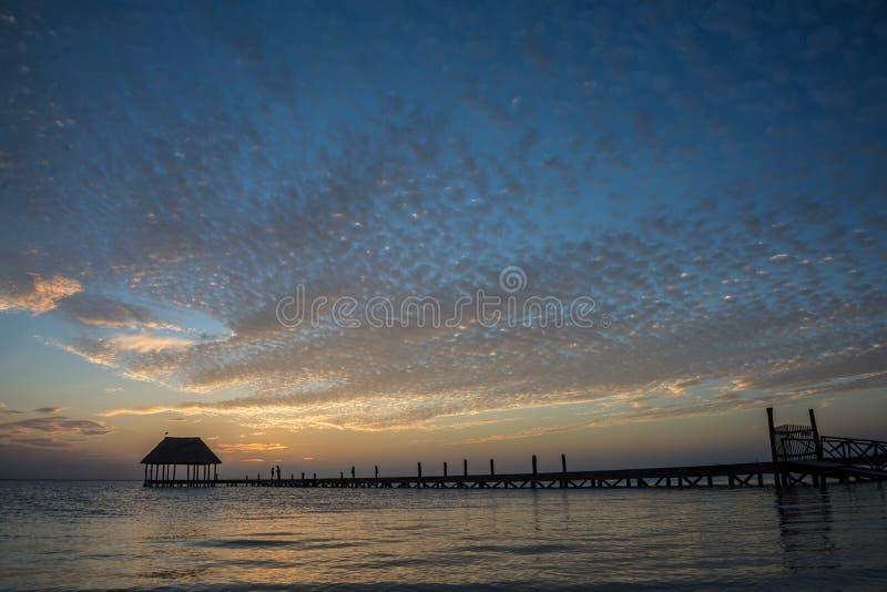 Pares en amor en un palapa de madera del embarcadero que disfruta de puesta del sol en Holbox foto de archivo libre de regalías