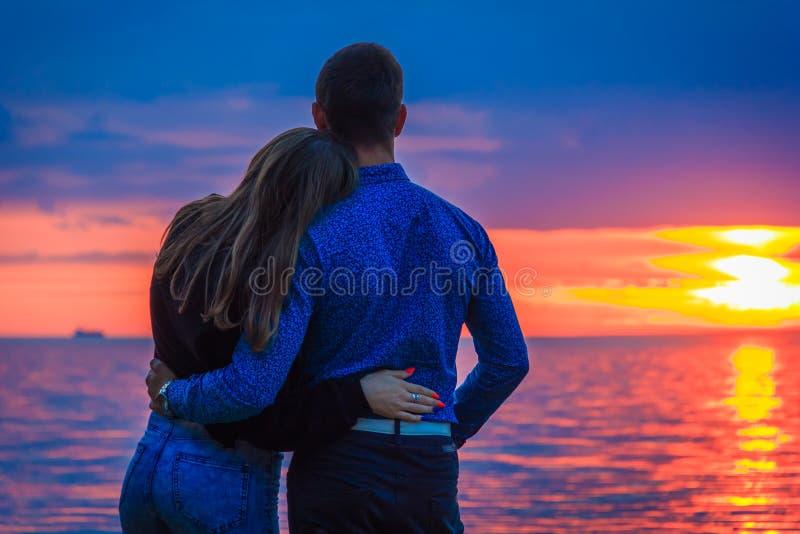 Pares en amor en la puesta del sol por el mar fotos de archivo libres de regalías