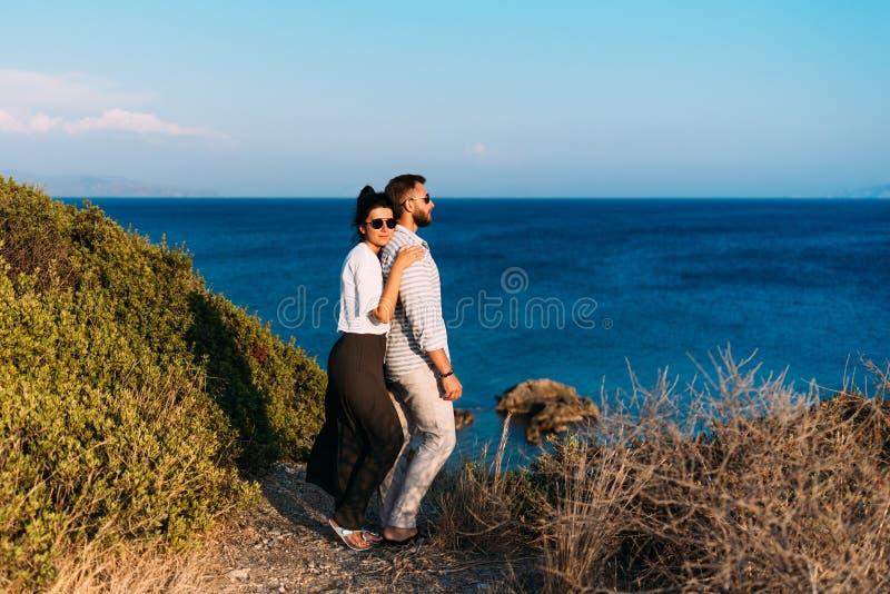 Pares en amor en la puesta del sol por el mar Pares felices en la puesta del sol honeymoon Viaje de la luna de miel Hombre y muje foto de archivo